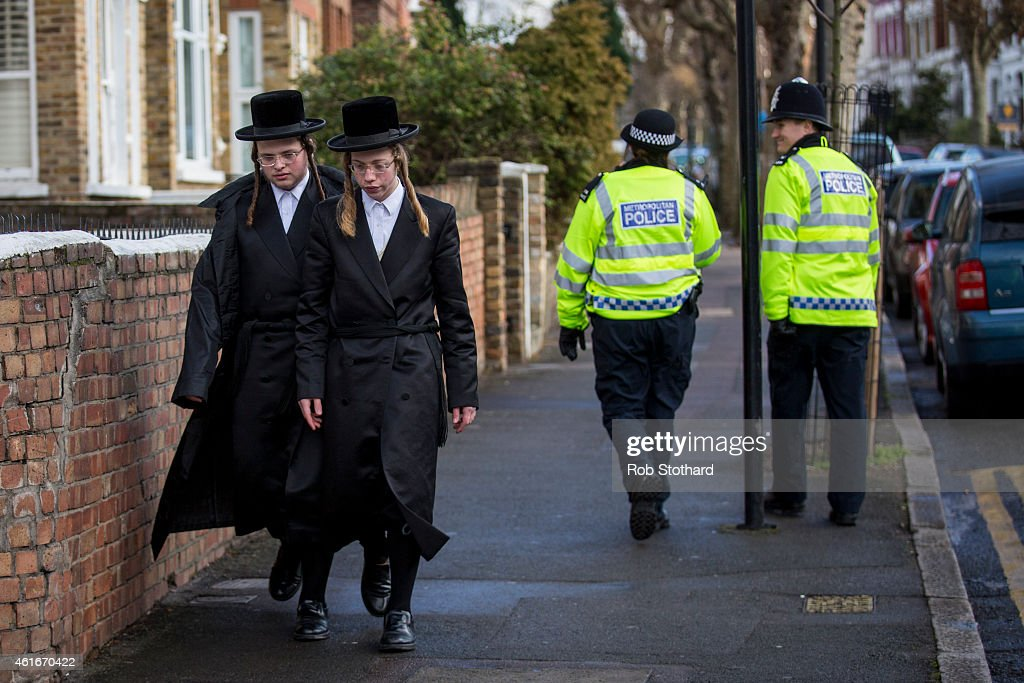 Jewish Men Walk Along The Street In The Stamford Hill Area
