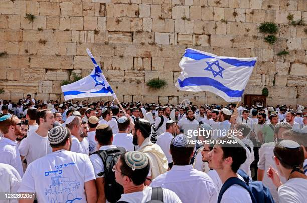 Jewish men wave Israeli flags as they gather at the Western Wall, the holiest site where Jews are allowed to pray, in the old city of Jerusalem on...