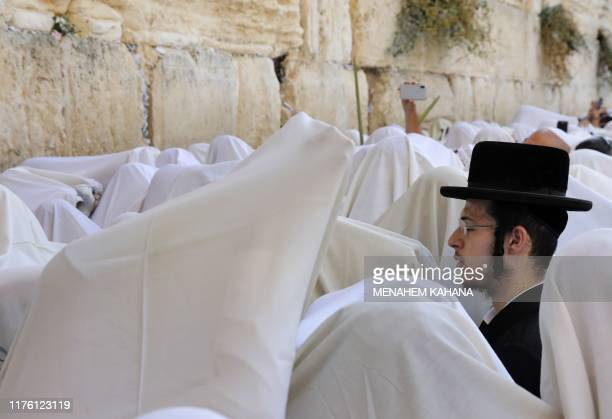 TOPSHOT Jewish men wearing the traditional Jewish prayer shawls known as Tallit perform the annual Birkat Kohanim during the Sukkot holiday or the...