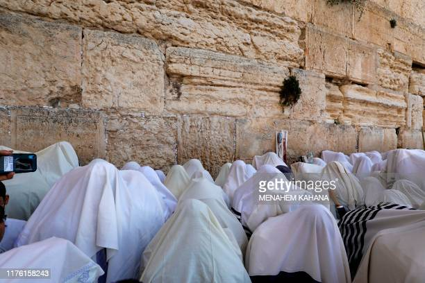 Jewish men wearing the traditional Jewish prayer shawls known as Tallit perform the annual Birkat Kohanim during the Sukkot holiday or the feast of...