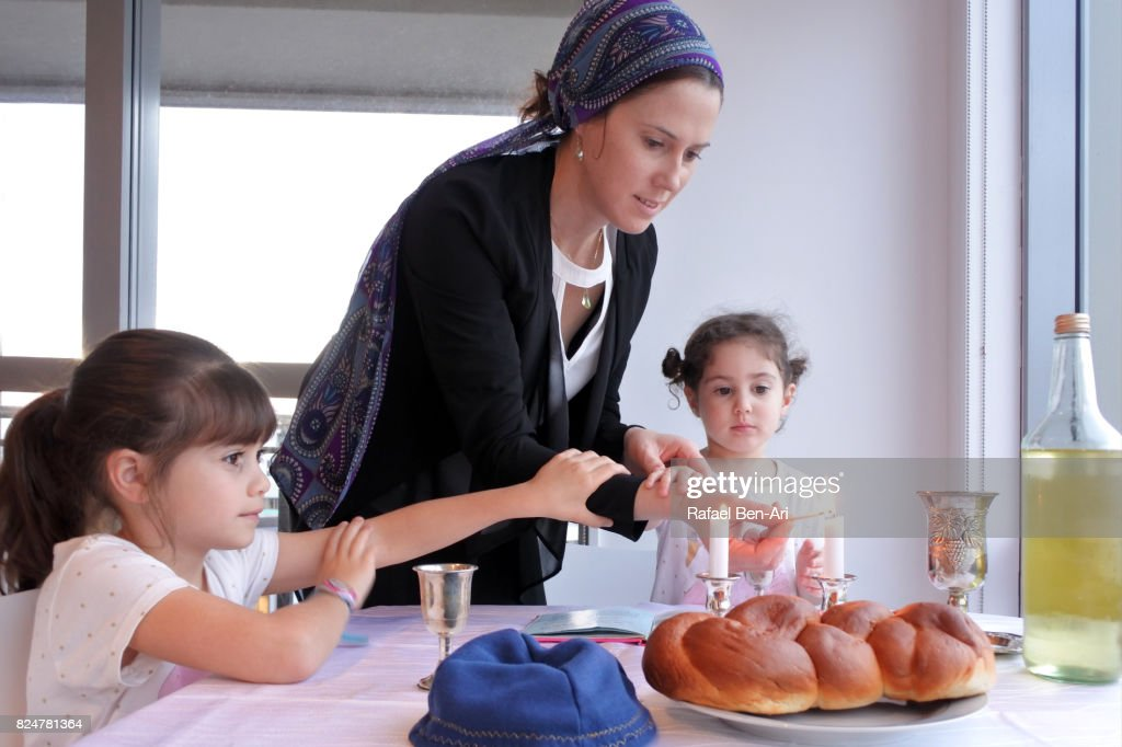 Jewish mother and daughters light Sabbath candles : Stock Photo