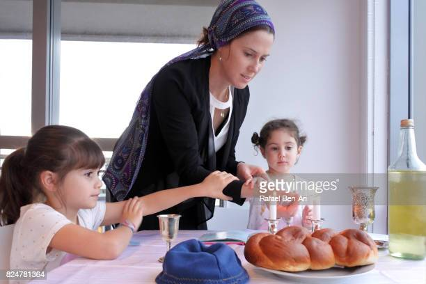 Jewish mother and daughters light Sabbath candles