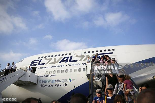 Jewish new immigrants from North America who are making Aliyah step off the plane upon their arrival at Ben Gurion International airport on August 12...