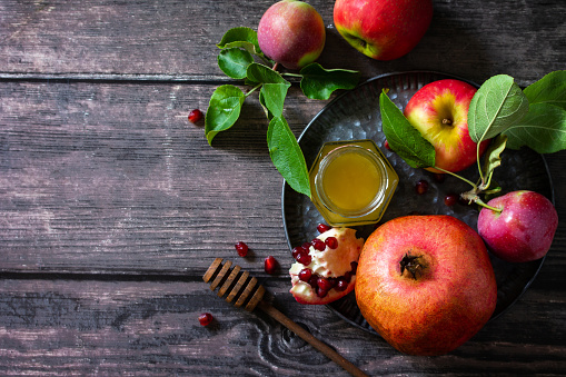 Jewish new year holiday concept. Traditional symbols: honey, fresh apples, pomegranate and shofar on a wooden table. Top view flat lay background. Copy space. 1260389201