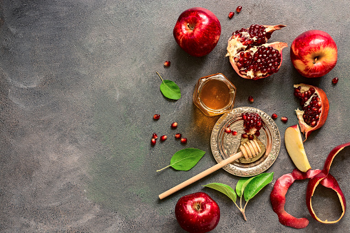 Jewish New Year - Rosh Hashanah. Apples, pomegranate and honey on a dark rustic background. Traditional Jewish food. Top view, flat lay,space for your text. 1159634089