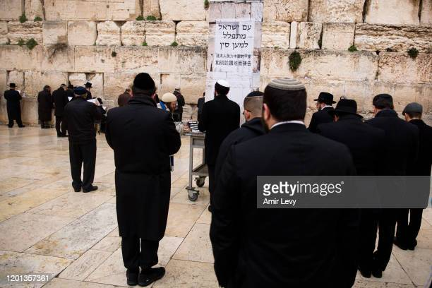 Jewish Orthodox men pray near a placarad reading in Hebrew 'Jewish People Pray for China' during a mass prayer at the Western Wall for coronavirus...
