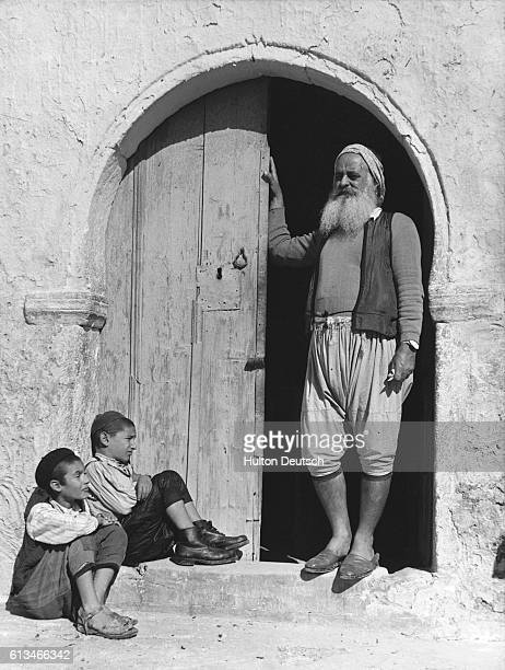 A Jewish patriarch stands with two boys in a doorway of a building on Djerba an island in the Gulf of Gabes where there is an ancient Jewish community