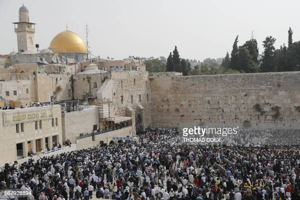 Jewish people take part in the Cohanim prayer during the Passover holiday at the Western Wall in the Old City of Jerusalem on April 13 with the Dome...