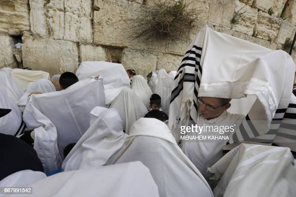 Jewish people wearing Talit take part in the Cohanim prayer during the Passover holiday at the Western Wall in the Old City of Jerusalem on April 13...