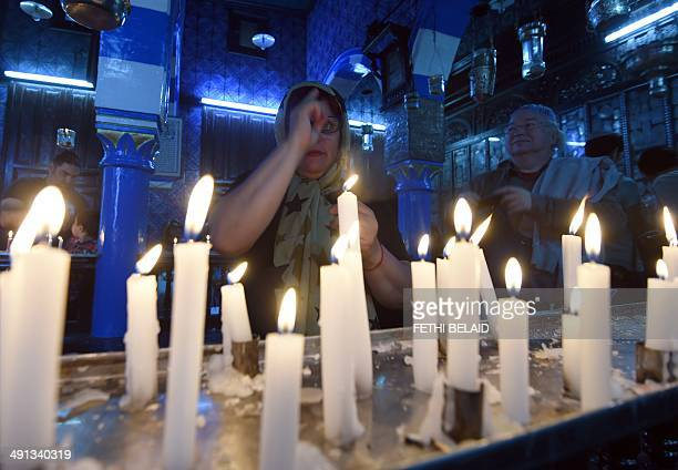 Jewish pilgrims light candles in the Ghriba synagogue on the Tunisian resort island of Djerba at the start of a threeday annual pilgrimage on May 16...