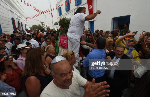 Jewish pilgrims take part in the procession of the Menara a hexagonal pyramid representing prophet Moses' five books outside the Ghriba synagogue in...