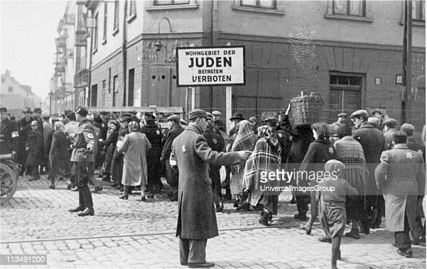 Jewish policeman and a German soldier direct pedestrian traffic across the main street dividing the two parts of the Lodz ghetto Poland Second World...