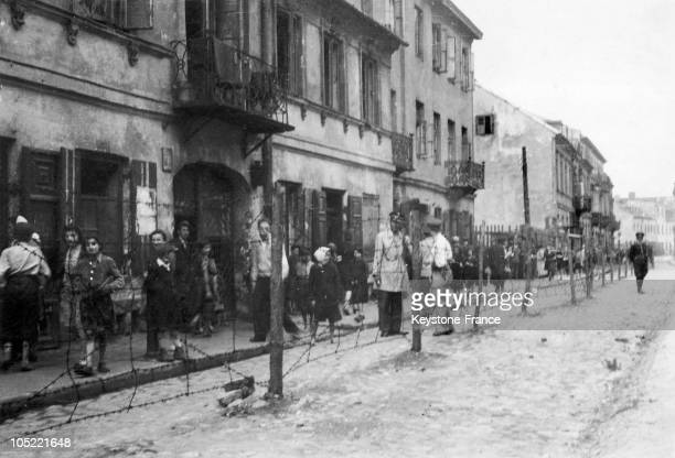 Jewish Population Behind Barbed Wires Which Stung Warsaw Ghetto From 1940 To 1943In The Middle Some German Soldiers Mounting Guard