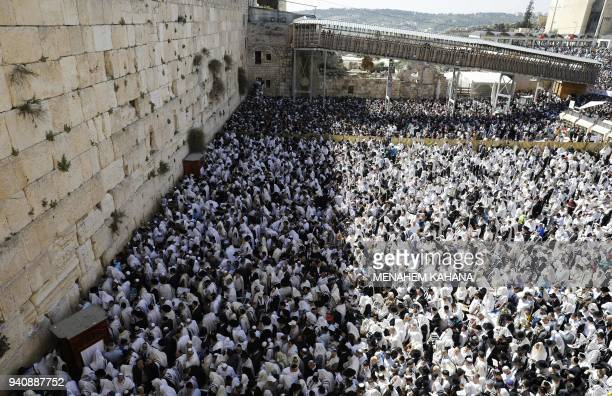 TOPSHOT Jewish priests wearing Talit and civilians take part in the Cohanim prayer during the Passover holiday at the Western Wall in the Old City of...