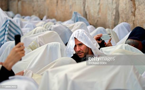 TOPSHOT Jewish priests wearing Talit prayer shawls take part in the Cohanim prayer during the Passover holiday at the Western Wall in the Old City of...