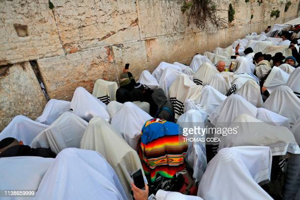 TOPSHOT Jewish priests wearing Talit take part in the Cohanim prayer during the Passover holiday at the Western Wall in the Old City of Jerusalem on...