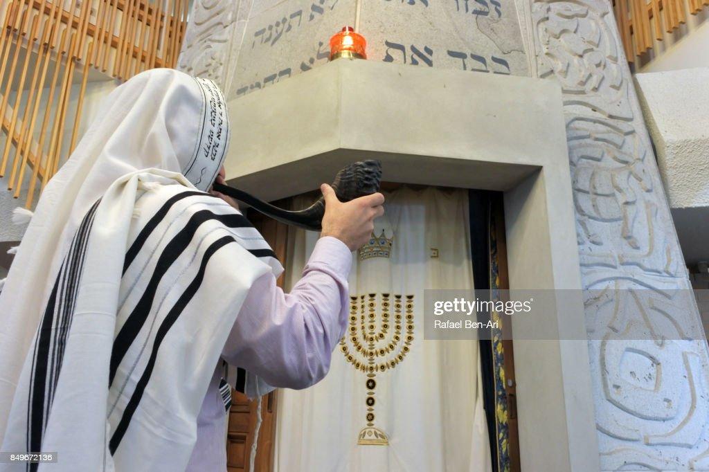 Jewish Rabbi blows Shofar in a synagogue : Stock Photo