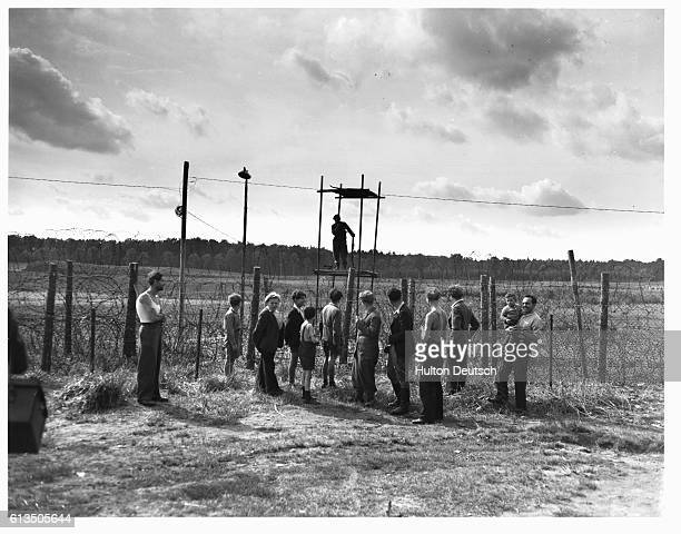 Jewish refugees from the 1947 Exodus ships stand inside the barbed wire enclosure of the Poppendorf displaced persons camp waiting out their release...