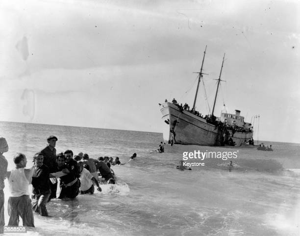 Jewish refugees swim to shore from the SS 'United Nations' which deliberately ran agound at Nahariya near Haifa carrying 700 central European Jewish...
