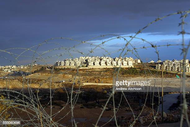 Jewish settlement in Palestine. Looking at it through a barbed wire barrier of the security fence.