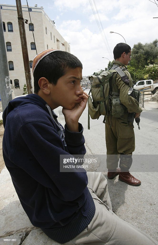 A Jewish settler gestures as he watches Israeli forces guarding a group of left-wing Israelis who came to visit Palestinian families in the divided West Bank city of Hebron on April 23, 2010. US envoy George Mitchell met Israeli Defence Minister Ehud, kicking off a day of talks with senior Middle East officials aimed at restarting peace negotiations.