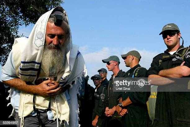 A Jewish settler prays alongside Israeli police who tried to secure the entry of shipping containers for settler families looking to evacuate August...