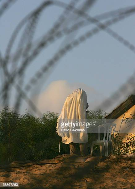 Jewish settler prays wearing a prayer shawl on August 17 2005 in the settler's outpost of Kerem Atzmona in the Gaza Strip Twelve resident families...