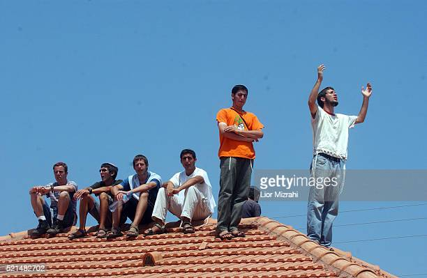 A Jewish settler shouts from a rooftop as others look on in the Jewish settlement of Neve Dekalim part of the Gush Katif settlement bloc Gaza Strip...
