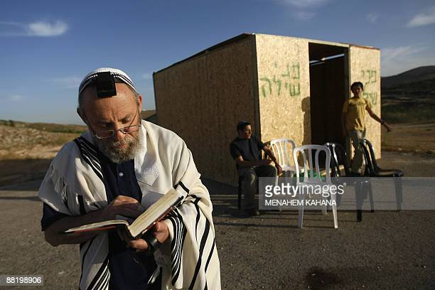 A Jewish settler wearing a prayer shawl recites prayers next to a wooden cabin built outside the West Bank settlement Shilo on June 4 the day after...