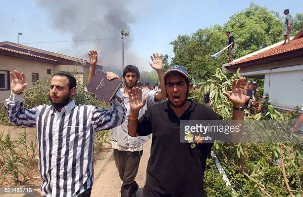 A Jewish settler wearing a replica of the Naziera shirt prays as he and others watch a house burning down in the Gaza Strip settlement of Neve...