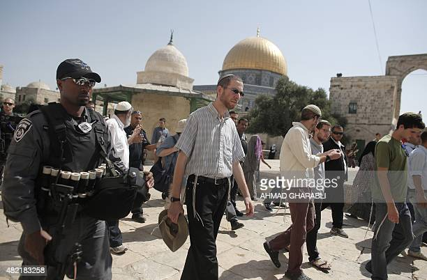 Jewish settlers accompanied by Israeli security guards walk past the Dome of the Rock during a visit to the AlAqsa mosques compound Islams third...