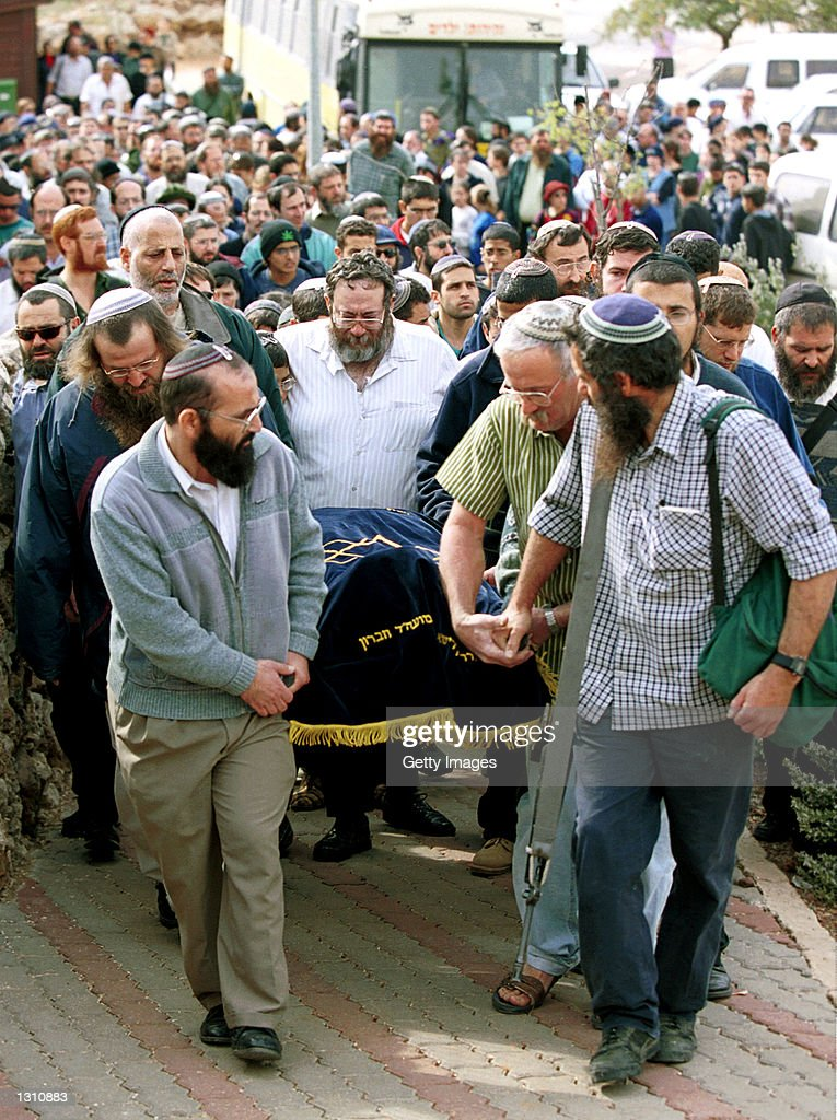 Jewish settlers carry the shroud-covered body of Hannah