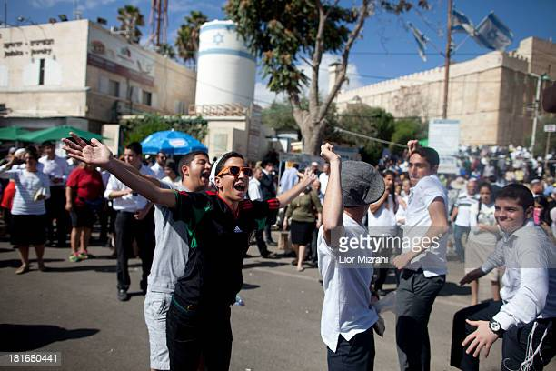 Jewish settlers dance outside the Tomb of the Patriarchs on September 23 2013 in Hebron West Bank Israeli security forces showed strong presence in...