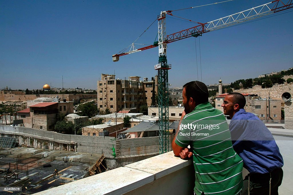Jewish settlers look down on a building site for an extention to the Maale Zeitim (Olive Heights) religious settlement on the Mount of Olives August 18, 2008 in East Jerusalem, Israel. The settlement, an apartment complex which houses dozens of families, is being built with funding from the Florida-based bingo and gambling magnate Irving Moskowitz by the Ateret Cohanim organization, which is dedicated to expanding Jewish settlement in East Jerusalem, the half of the city that Israel captured from Jordan in the 1967 Six Day War.