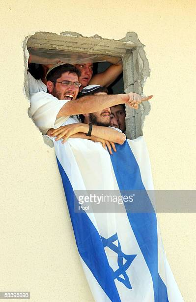 Jewish settlers shout and point through an open window of a house August 17 2005 in the southern Gaza Strip settlement of Morag Thousands of Israeli...