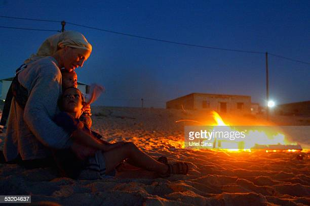 Jewish settlers sit by a fire at the Mediterranean shore July 6 2005 at the Jewish Gaza Strip settlement of Shirat Hayam in the Gush Katif...