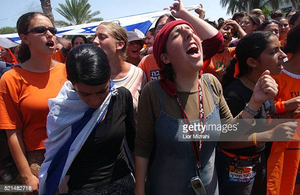 Jewish settlers, some wearing Israeli flags, dance and sing in front of Israeli soldiers and police officers outside the synagogue of the Jewish...