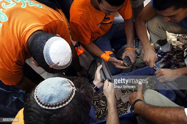 Jewish settlers unload ammunition before handing over their weapon to the Israeli army at the Jewish settlement of Netzer Hazani in the Gush Katif...