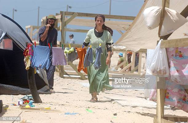 Jewish settlers walk amongst partially constructed shelters that is part of a camp to be used by settlers opposed to the Gaza withdrawal later this...