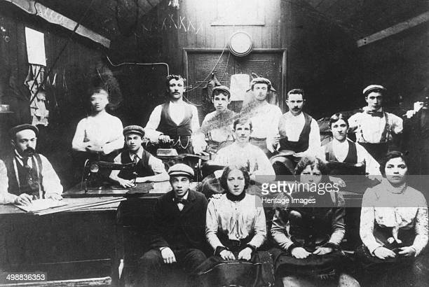 Jewish tailoring workshop in London's East End c1910 Employees with the tools of their trade tape measures sewing machines and unfinished suits