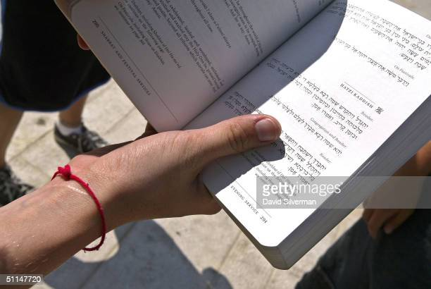 Jewish teenage girl wears her Kabbalah Red String Bracelet while praying at the Western Wall Judaism's holiest site August 6 in Jerusalem's Old City...