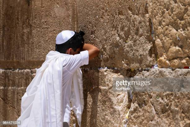 Jewish teenager prays during a bar mitzvah ceremony at the Western Wall in Jerusalem, Israel on June 25, 2018. The Western Wall also called the...