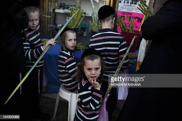 Jewish UltraOrthodox children waits for their father who is buying the myrtle branch one of four species used during the celebration of Sukkoth the...