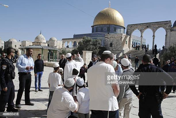 Jewish visitors stand outside the Dome of the Rock mosque at the alAqsa mosque compound in Jerusalem as they enter the area under Israeli security...