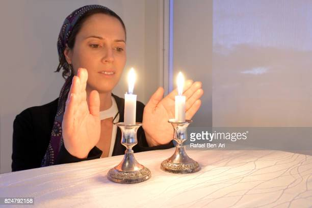 jewish woman lights sabbath candles - rafael ben ari stockfoto's en -beelden