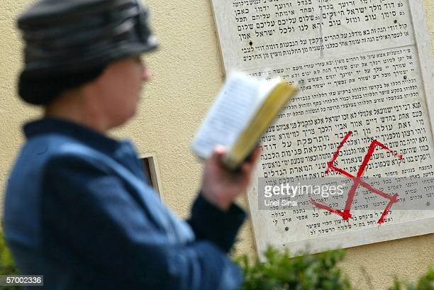 A Jewish woman prays near antisemitic graffiti which was sprayed on the walls of a synagogue March 5 2006 in Petah Tikva near Tel Aviv in central...