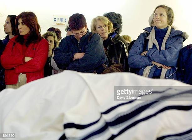Jewish women grieve over the prayer shawlcovered body of IsraeliAmerican Avi Boaz during his funeral January 16 2002 in Jerusalem a day after he was...