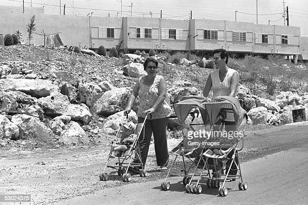 Jewish women settlers walk their infant children past housing July 25 1980 at the West Bank settlement of Ariel Established in 1978 this settlement...