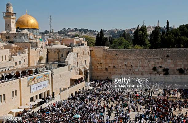 Jewish worshippers perform prayers during the holiday of Sukkot at the Western Wall in the Old City of Jerusalem on September 26 2018
