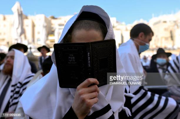 Jewish worshippers pray at the Western Wall during the Priestly Blessing on the holiday of Passover, in Jerusalem on March 29, 2021.